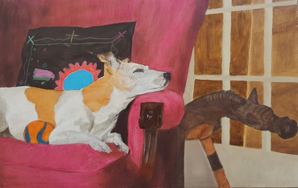 A sleeping Jack Ruseell terrier on a chair, with an animal sculpture next to him